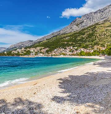 Turquoise seas lap against a shingle shore along the Makarska Riviera