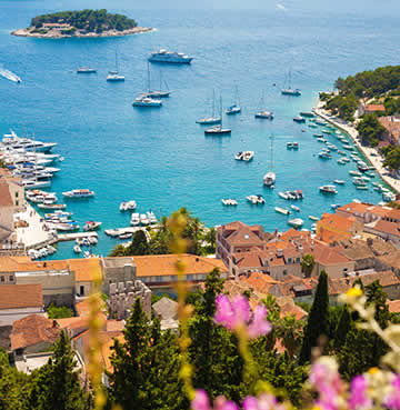 A bird's eye view of Hvar Town harbour, luxury yachts line the marina