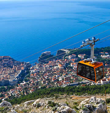 An orange cable car takes passengers from Dubrovnik's Old Town to the top of Mount Srđ
