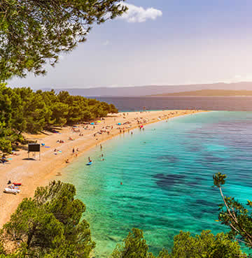 Holidaymakers relax on the 'golden horn' of Zlatni Rat Beach on the island of Brac
