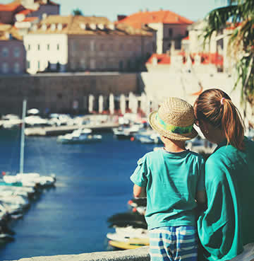 A mother and son looking across the Old Town harbour to the Walls of Dubrovnik