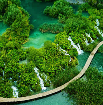 An aerial view of a wooden walkway and waterfalls at Plitvice National Park in Croatia
