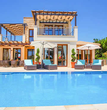 A large swimming pool and luxury patio area in front of a private villa