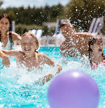 A young family splashing about in their villa's private swimming pool with a purple inflatable ball.