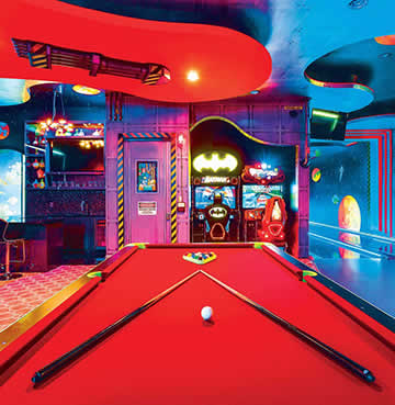 A child's fantasy gaming room, including pool table, arcade games, games consoles and a bespoke, two-lane bowling alley