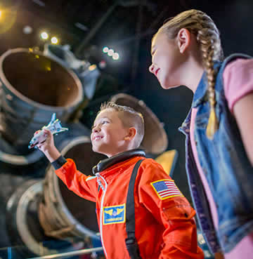 A brother and sister at Kennedy Space Center Visitor Complex. The young boy holds a replica model of the Shuttle Atlantis spaceship, while a full size spaceship is hanging from the hanger ceiling above.