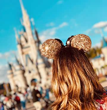 A young tween wearing Mickey Mouse ears at Magic Kingdom, Walt Disney World Resort, Orlando