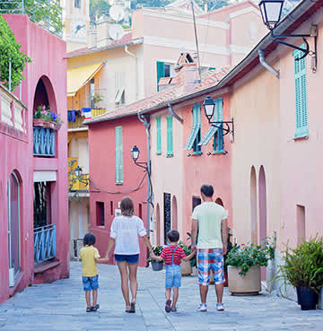 A family walk hand in hand along a narrow street lined with pink houses in a Provençal village.