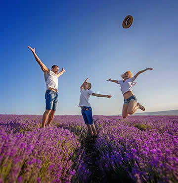 A young family jumping in a lavender field in Provence