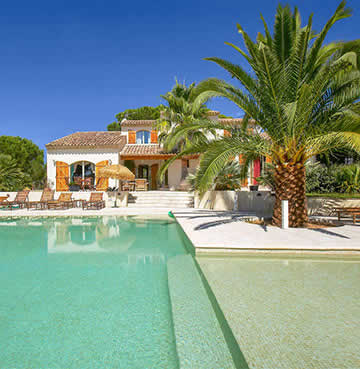 A luxurious whitewashed villa in the Cote d'Azur, surrounded by luscious palm trees and a huge private swimming pool