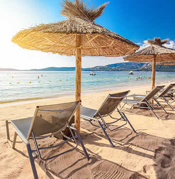Straw umbrellas and luxury sunloungers lining a powder-white, sandy beach in Corsica
