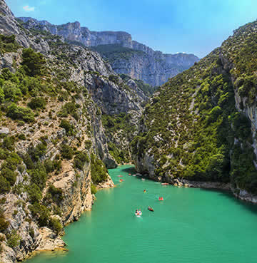 Towering canyon carpeted in luscious greenery, overlooks aquamarine waters of the Verdon River at the Verdon Gorge