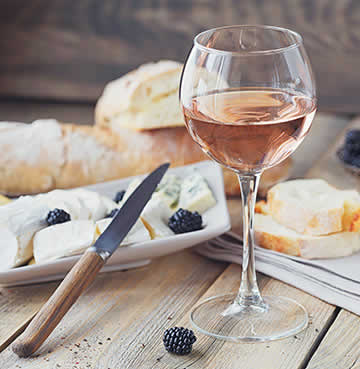 A glass of Rose wine and a plate of cheese are placed on a rustic table