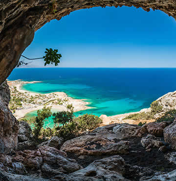 Looking through a cliff cave opening to the beautiful beach of Balos in the distance