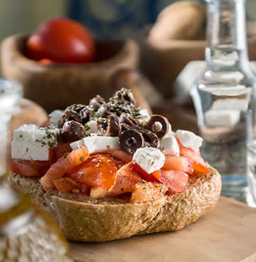 Traditional Dakos covered in tomato and crumbled soft cheese