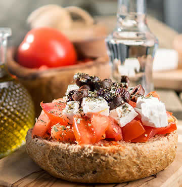 Traditional Cretan food of freshly prepared tomatoes and cheese on a bread roll
