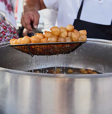 A chef scoops out freshly made loukoumades from the fryer at a market in Crete