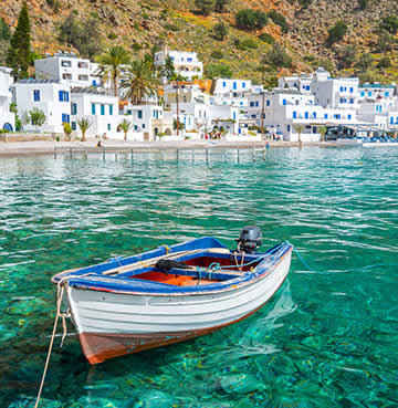 A fishing boat floats on azure seas in Crete