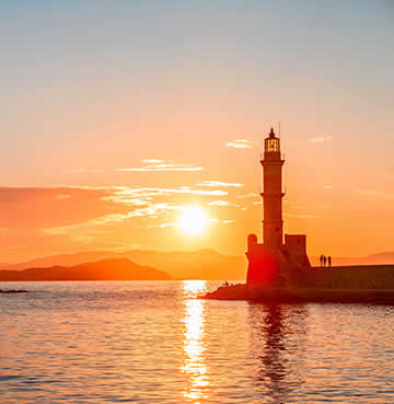 The Venetian harbour and famous lighthouse in Chania at sunset