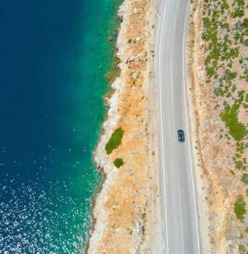 Aerial view of a coastal road running parallel to azure seas and a craggy shoreline, a blue car is on the road