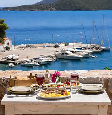 Traditional meze is laid out on a wooden taverna table at a quiet harbour in the Greek Islands