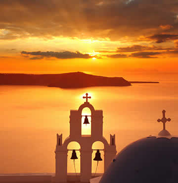 A church steeple and blue dome frames a golden Santorini sunset, with views over the caldera and out to sea