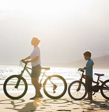 A mother and son on a beach in the Algarve with their bikes
