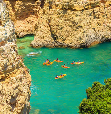 A group of yellow kayaks in the azure sea water of the Algarve