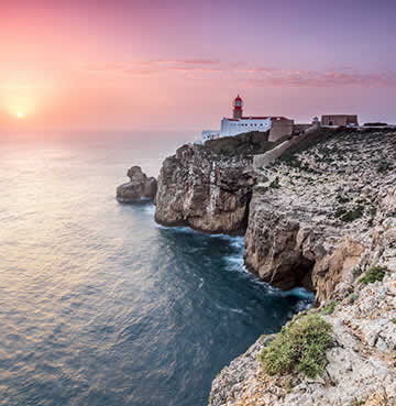 The lighthouse and craggy cliffs of Cape Sant Vincent at sunset