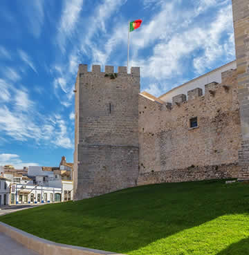 Loule castle, fronted by a grassy bank, with a small selection of traditional houses in the background.