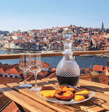 Pastel de nata and a bottle of wine sit on a wooden table, overlooking the river and skyline of Porto