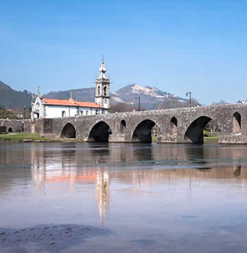 A long, arched bridge crosses a wide river. A traditional church sits in the background.