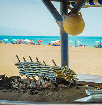 Sardine skewers being traditionally cooked in a boat over hot coals on the beach