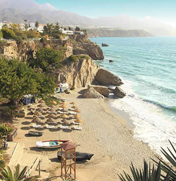 Calahonda Bay, waves rolling up the beach, which is surrounded by cliffs and agricultural land.