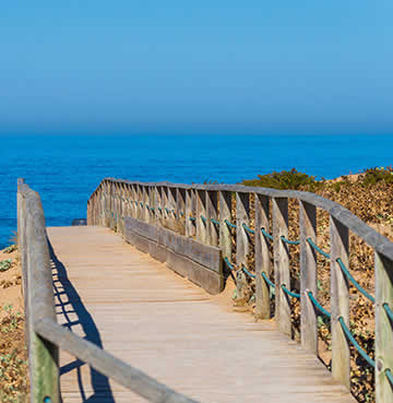 Wooden walkway leading to Playa Del Palmar surrounded by greenery. Blue seas are on the horizon with a blended blue sky.