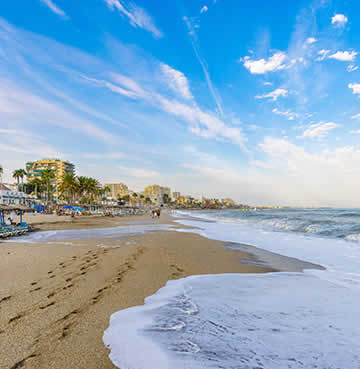 Tides rolling against golden shores at a beach in Benalmadena