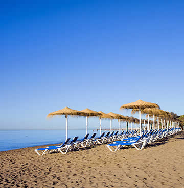 Sunloungers and straw parasols on a beach in Marbella