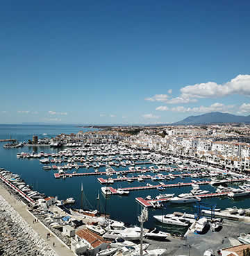 Aerial view of whitewashed architecture and yacht-filled marina in glamorous Puerto Banus.