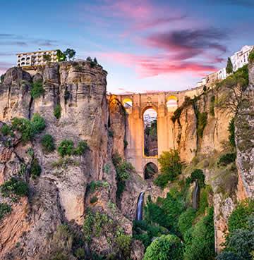 Puente Nuevo Bridge, El Tajo gorge and the rustic village of Ronda at sunset.