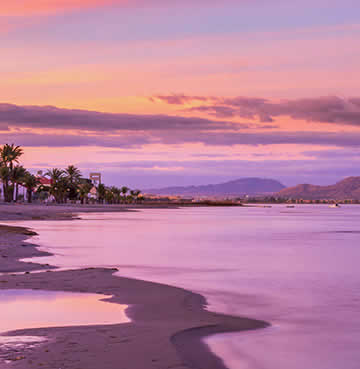 Coastal lagoon at La Manga Del Mar Menor at sunset. The sky is painted in different shades of soft purple, white the water laps gently at the beach.
