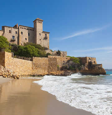 A Roman castle stands watch over a small cove in the region of Tarragona, Costa Dorada