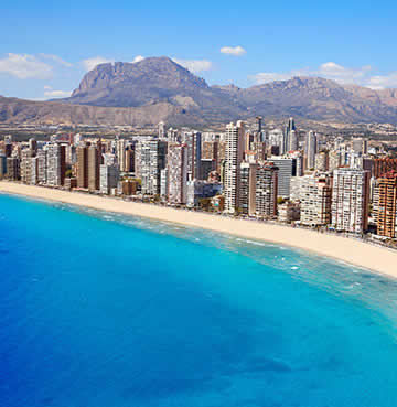 High-rise skyscrapers sit against a backdrop of majestic mountains. Powder-white sands and turquoise waters are the centerpiece of the scene at Playa de Levante, Benidorm