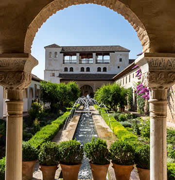 Landscaped gardens at Granada's Alhambra Palace, looking through an archway towards a series of water fountains