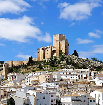 A Moorish castle sits on top of a hill in Almeria, overlooking a traditional Spanish whitewashed village