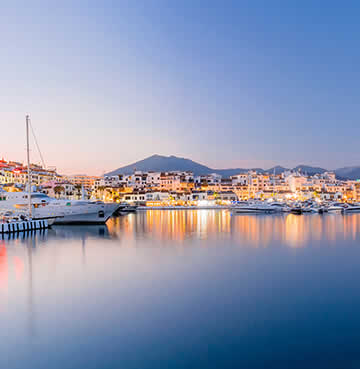 Puerto Banus' modern marina at dusk, with luxury yachts anchored in the harbour