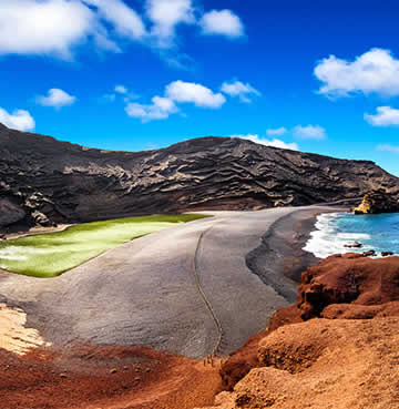 Blue sea waters crash against black volcanic sands. Red cliffs line the scene and a green lake sits in the middle of the beach.
