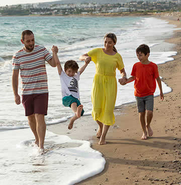 A young family walk along a golden beach, mum and dad swing their youngest between them.