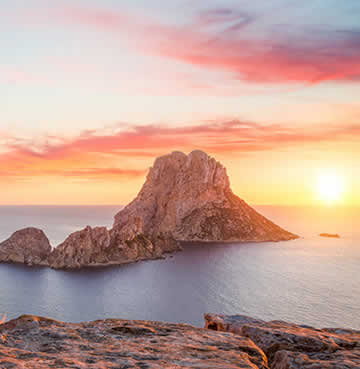 A pink sky at sunset over the iconic Ibiza spot at Es Vedra