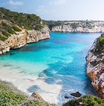 Turquoise seas lap gently against silver soft sands at Calo des Moro beach