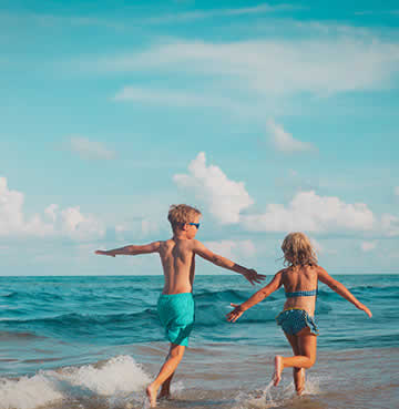 Brother and sister run along a beach in their swimwear. The azure waves are gently lapping at their ankles.